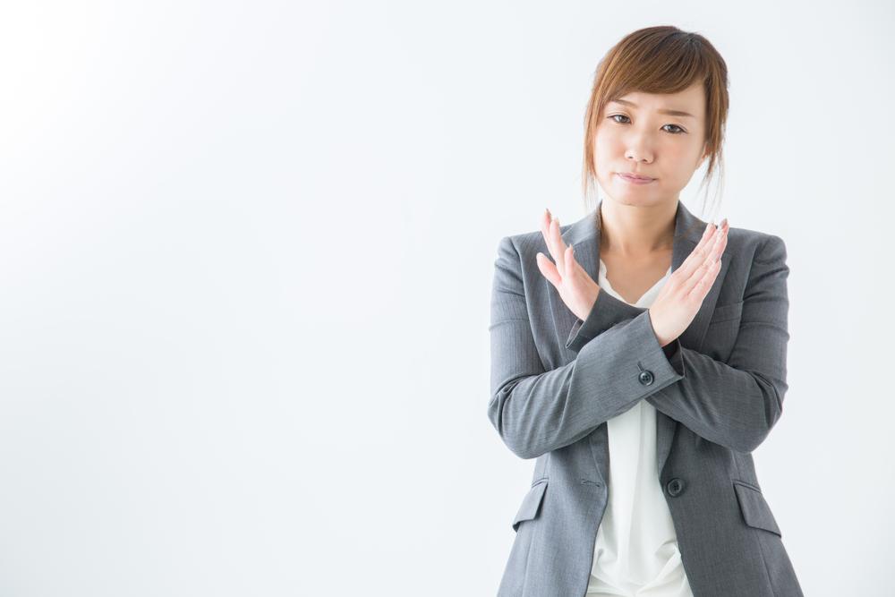 両手でバツ印をする女性